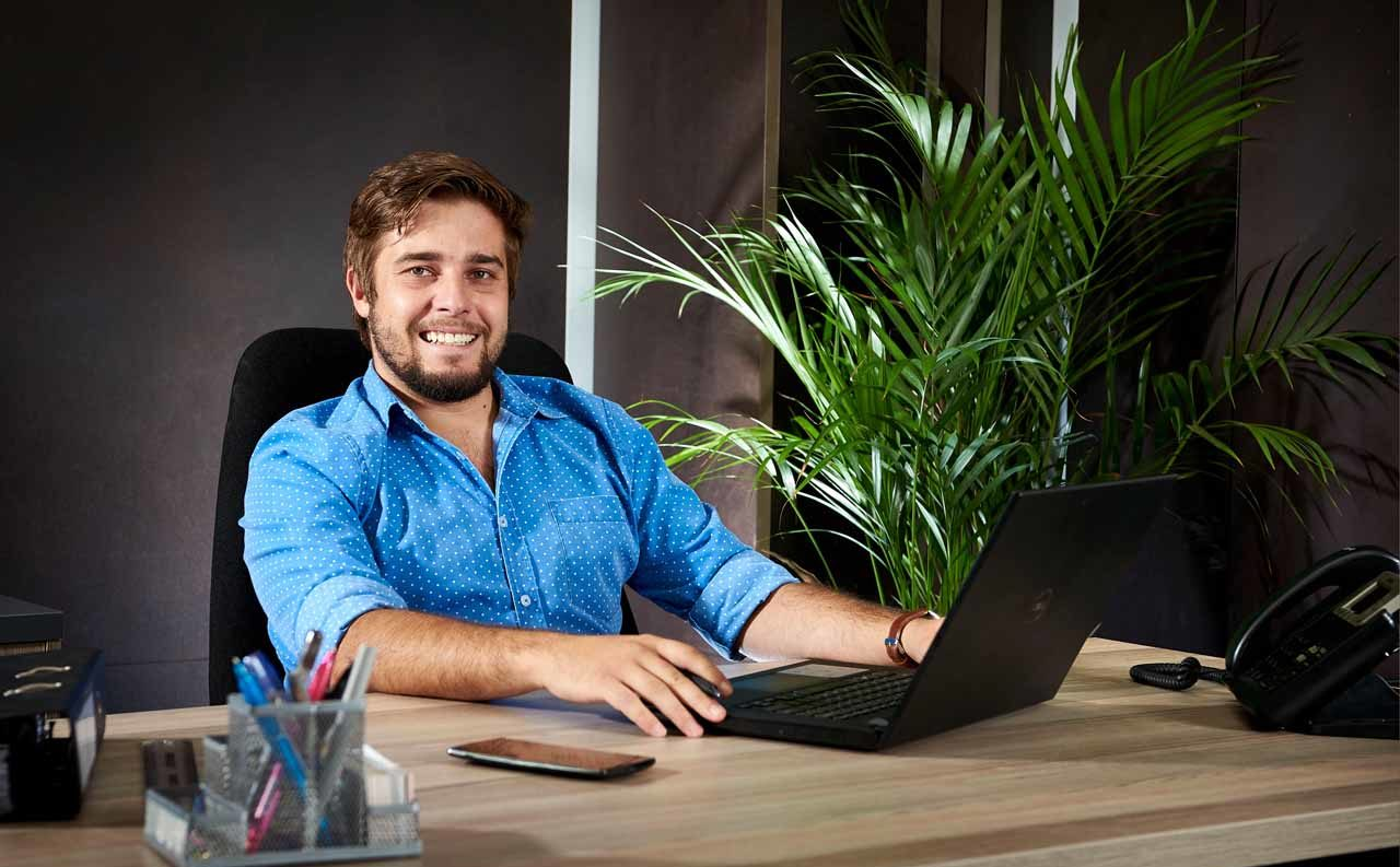 A young male office worker working on his laptop in an office at The Workspace
